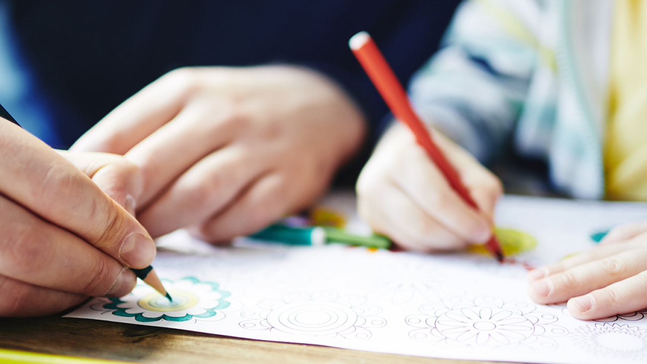 Parent and kid colouring pictures with pencils