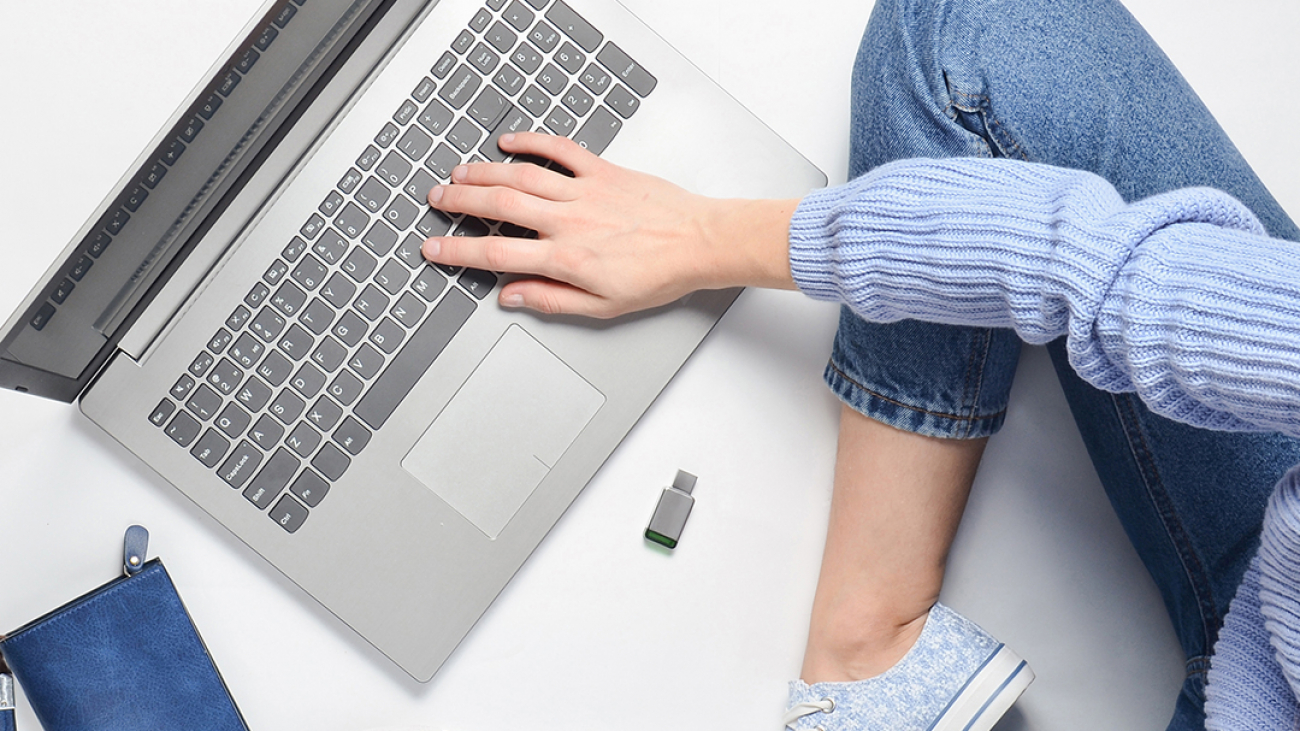 A modern young girl sits on a white floor and use a laptop.