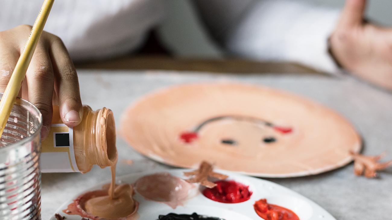 Kid painting reindeer on a paper plate