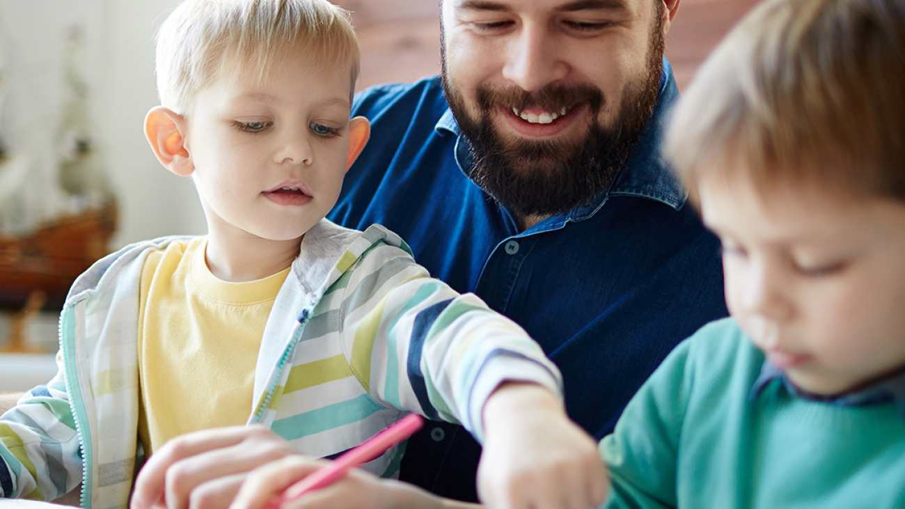 Little boy pointing at his brother drawing whilst sitting on dad's lap