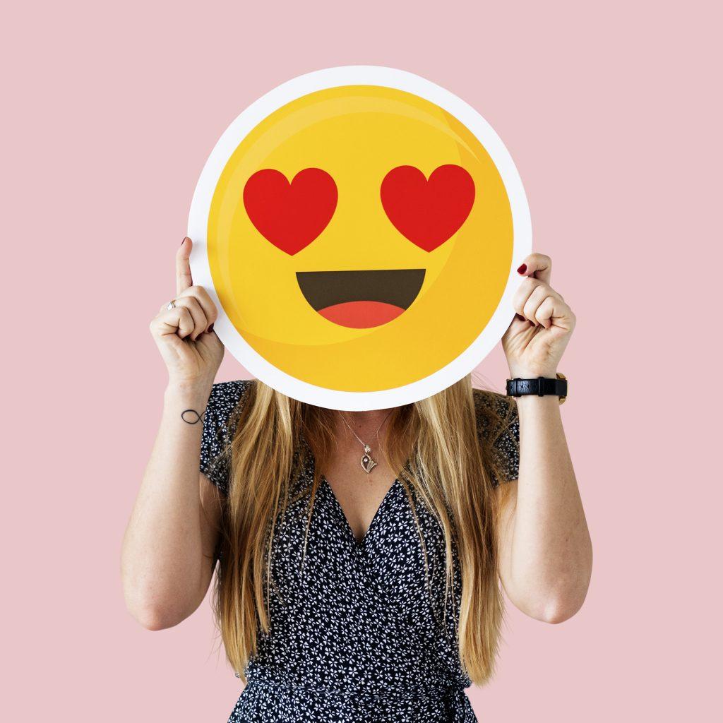 Woman holding heart emoji mask