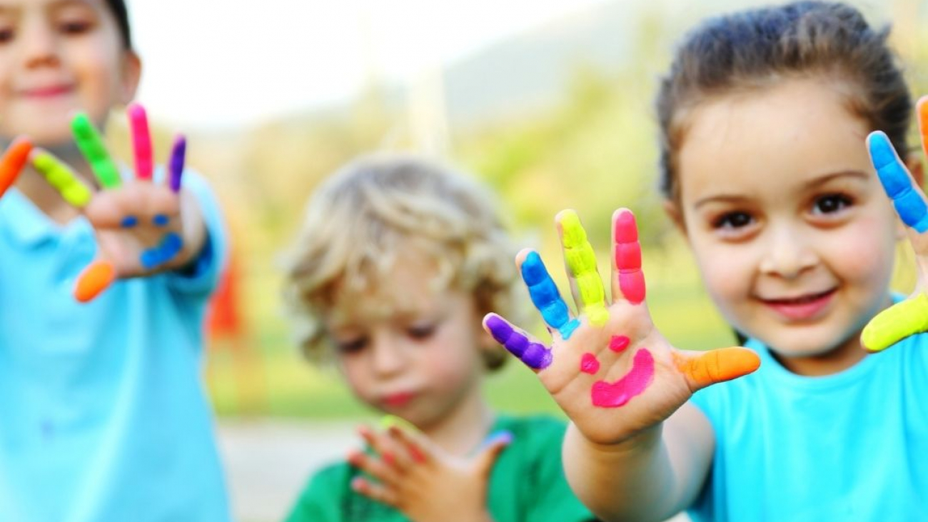Children with smiley faces painted on hands