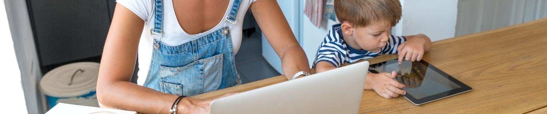 Mum on laptop, child on tablet